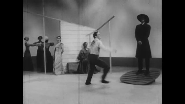 1950s: Man spins and dances ballet on stage before women and parson.