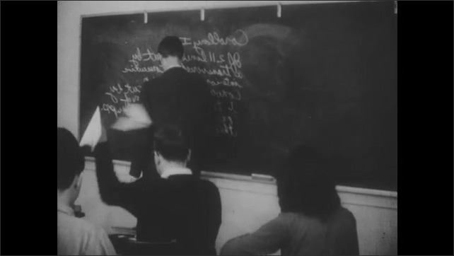 1960s: UNITED STATES: students throw paper planes behind teacher's back. Girl dances with arms. Man turns around from blackboard. Students pretend to work