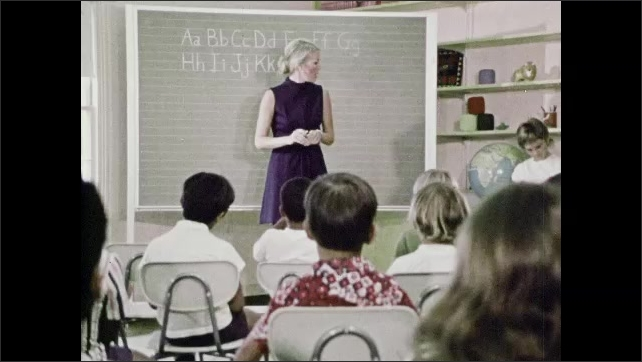 1970s: A girl. A girl. Another girl. Children in classroom are playing around. Woman at front of class talks and children sit in chairs. Girl stands at front of class with book then sits in chair.