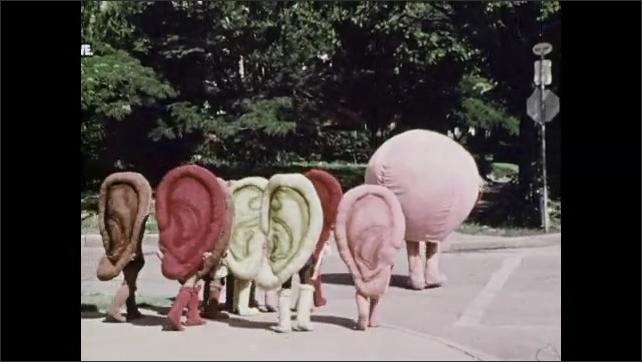 1970s: Person in giant mouth costume talks at intersection with children in ear costumes. They walk across street.
