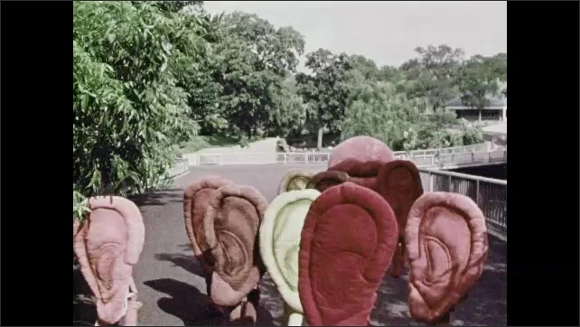 1970s: Person in giant mouth costume walks backwards on path leading children in ear costumes.
