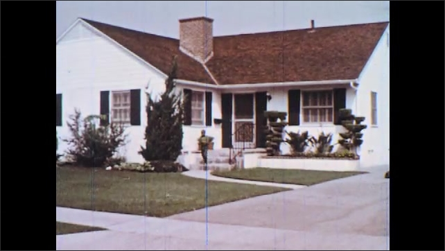 1960s: Neighborhood.  Woman walks down sidewalk.  Boy comes out of house and falls to the ground.  Girl stops and looks.