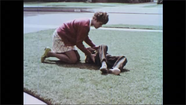 """1960s: Young woman drops books and rushes to help boy rolling on ground.  Girl checks boy.  Text reads """"GET HELP!""""  Girl stands in kitchen."""