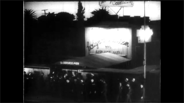 1940s: Neon lit sign for Hollywood Canteen. Large crowd of people enter the front to the Hollywood Canteen nightclub.