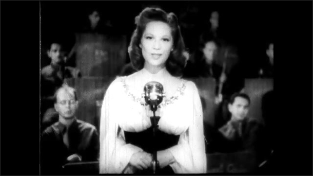 1940s: Soldiers sit in audience at nightclub, clapping. Dinah Shore stands on stage talking into microphone. Dinah Shore standing on stage in front of band, talking into mic.