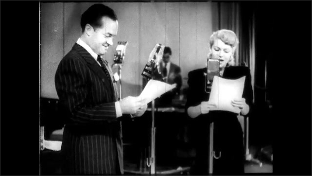 1940s: UNITED STATES: Lady arrives on stage. Man sets up microphone for lady. Man and lady read notes on stage.