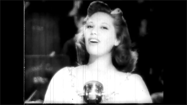 1940s: Dinah Shore stands on stage behind microphone, singing, while band performs behind her.