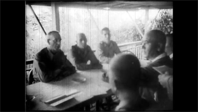 1940s: Japanese soldiers prepare for battle. Soldier cleans gun. Soldiers exiting boats. Soldiers climbing hill. U.S. officers sit at table, talking. U.S. flag on pole is replace by Japanese flag.