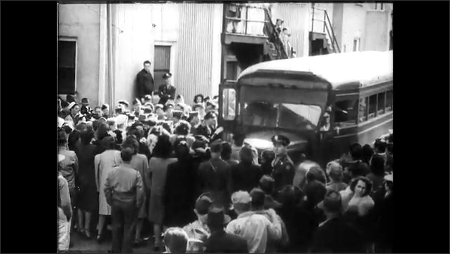 1940s: Children wave flags on parade route. Soldiers wave to crowd from buses. Soldiers exit bus and greet crowd. Amputee soldier walks down street.