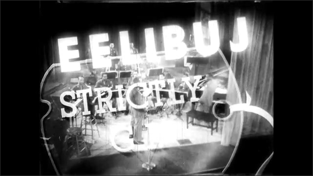 1940s: Statue of Liberty. Jubilee title screen. Curtain opens on small orchestra. Soldier walks to microphone and makes announcement.