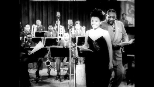 1940s: Men perform routine at mic. Lena Horne walks onto soundstage and approaches mic. Man and woman speak into microphone.