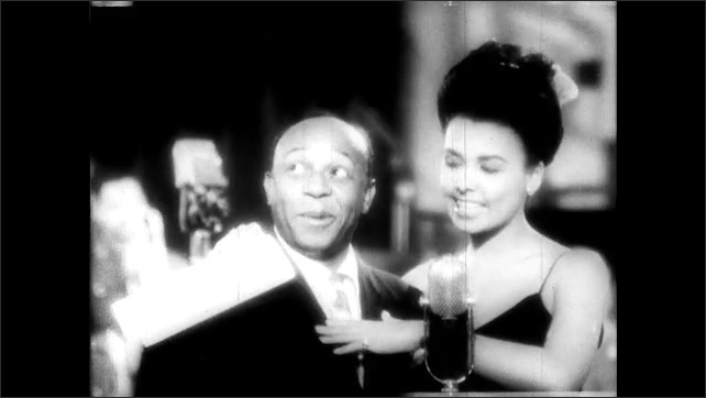 """1940s: Lena Horne sings and flirts on stage with Eddie """"Rochester"""" Anderson. Eddie Anderson looks amused."""