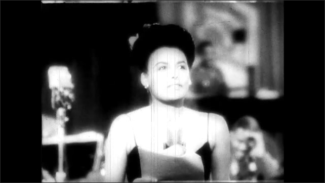 1940s:  Lena Horne at the mic gives a speech to the soldiers listening. Animation of radio towers and the globe spinning.