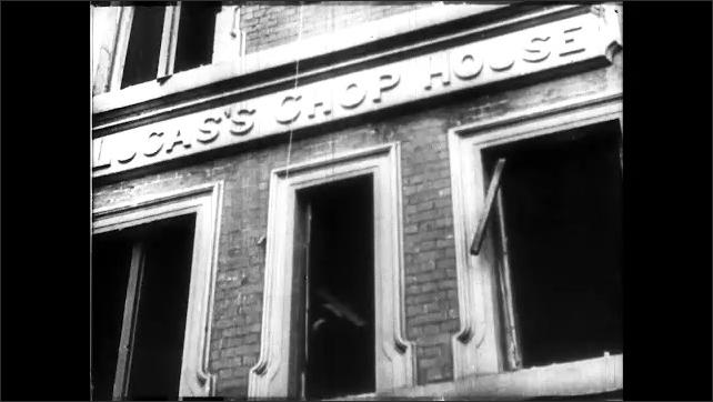 1940s: Girl climbs on mountain of rubble. Men climb over rubble. Restaurant facade. Rubble. Poster for hospital. Rubble.