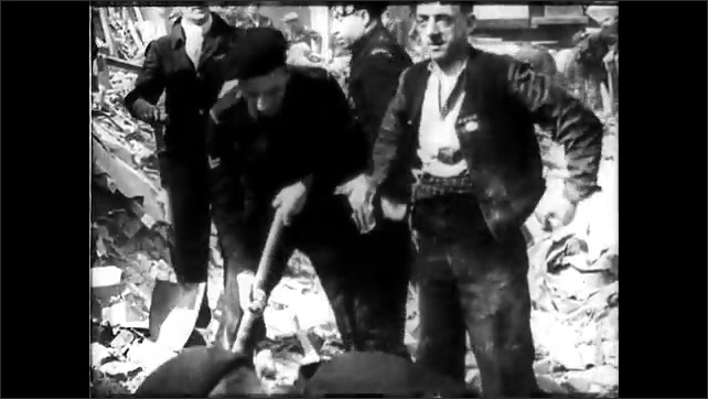 1940s: Men in uniform stand in line, mill about in street. Men excavate rubble. Ruins of building. Man sprays water from hose onto rubble.