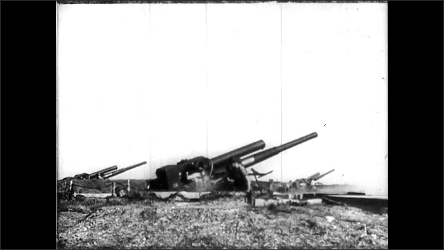 1940s: Plane flies through sky. Soldiers load large caliber ammunition into large weapon, fire weapon. Guns fire at planes in the sky, plane explodes.
