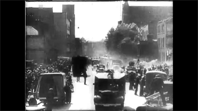 1940s: Street lamp. Smoke rises up from the middle of London. Cars and people crowd around bombed building. Men and women climb over rubble.