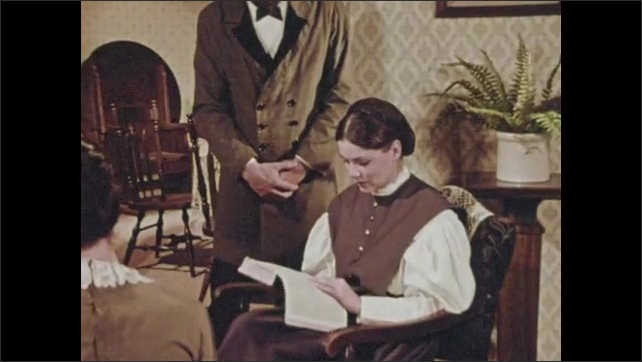 1970s: Scholar reads from book and stoops down to share with woman, pointing at page. Woman reads and rests hands under her chin.