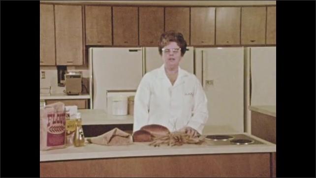 1970s: Woman standing in kitchen speaks.