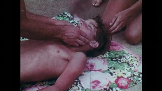 1960s: UNITED STATES: man carries boy from pool. Family resuscitate pool after pol accident. Man attempts artificial resuscitation of boy by pool