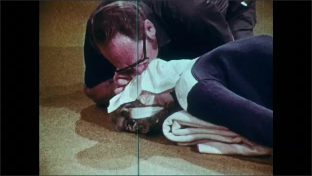1960s: UNITED STATES: man gives mouth to mouth resuscitation through handkerchief.