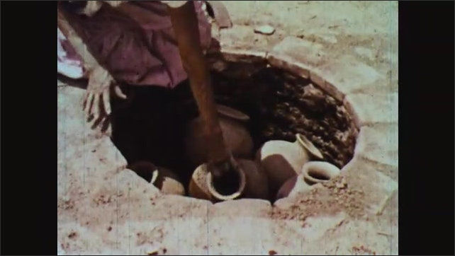 1960s: Woman places pots inside fire pit made of bricks.