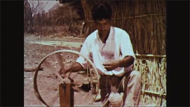 1960s: Woman runs wool through loom, making yarn. Man makes yarn on loom. Woman boils strips of cloth in pot. Man adds strips of cloth to pot.