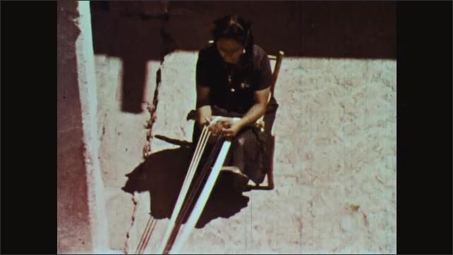 1960s: Woman turns wheel on loom as woman works behind her, weaving strings together.