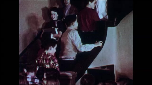 1950s: Students navigate crowded hallway. Students walk up and down stairs. Students slide trays along railing in cafeteria.