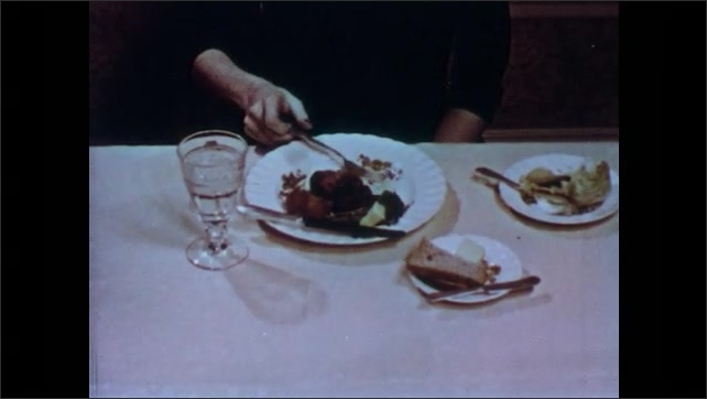 1950s: Woman eats meat at dining table. Woman breaks bread with hands. Woman spreads butter on bread with knife.