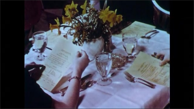 1950s: Girl and boy at table laugh and talk. Girl looks carefully at menu. Men and women order from menus at formal restaurant.