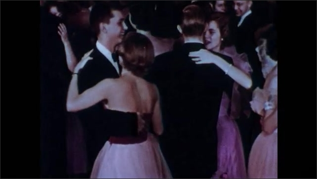 1950s: Teenage boys and girls in formal dress dance. Boys and girls mingle at formal dance.