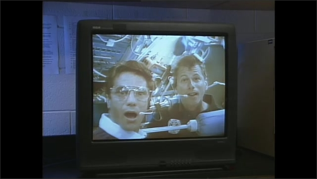 1990s: Man rides exercise bike while breathing into machine monitoring vitals. Two astronauts in space shuttle talk to each other on tv. Classroom watches tv then gathers around science lab table.