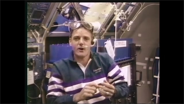 1990s: Hand places needle into tube. Student in classroom talks to astronaut floating in space shuttle on tv. Man in space shuttle talks to students. Hand writes on tube.
