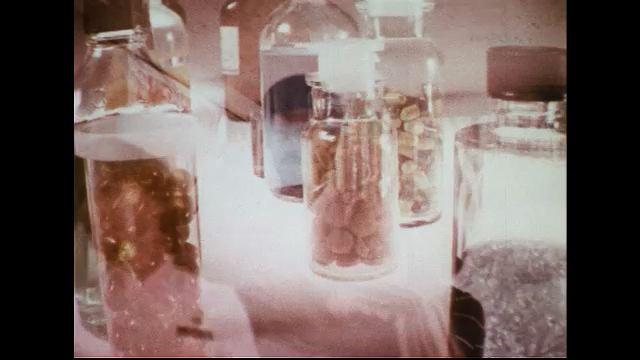 UNITED STATES 1970s: Close-ups of glass pill bottles on a white table.  What appear to be a child