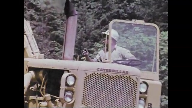 1970s: Construction equipment passing on road. Man driving construction equipment. Bulldozer dumping dirt in truck. Construction equipment hauling dirt.