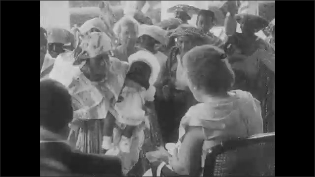 1950s: High angle of crowd. People walk in procession. People passing Queen Juliana. People walking. Woman shows doll to Queen. Women dancing in costume. Title over hourglass.