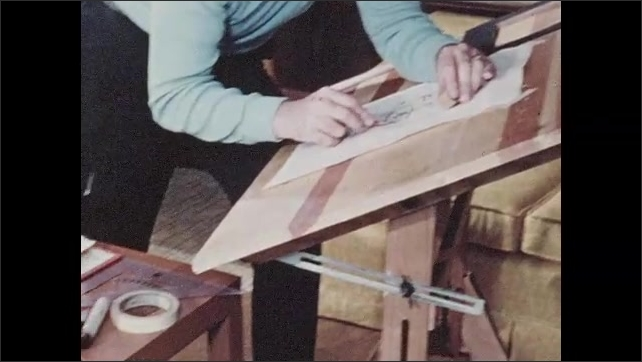1970s: Hands drawing, zoom out to man at table. Man drawing, pan to books on table.