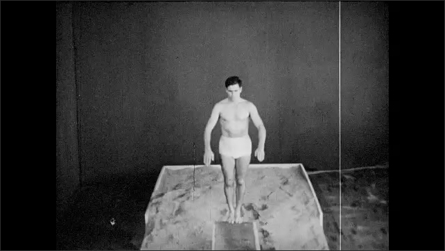 1950s: Feet walk and pivot on diving board and face backwards. Full body of male diver facing backwards on diving board and jumps into air. Male diver runs on diving board and springs up.