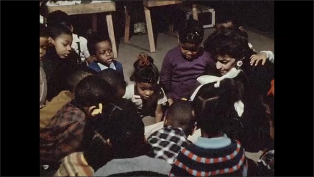 1970s: Group of mainly African-American kids sit cross legged on floor around a teacher, listening attentively.