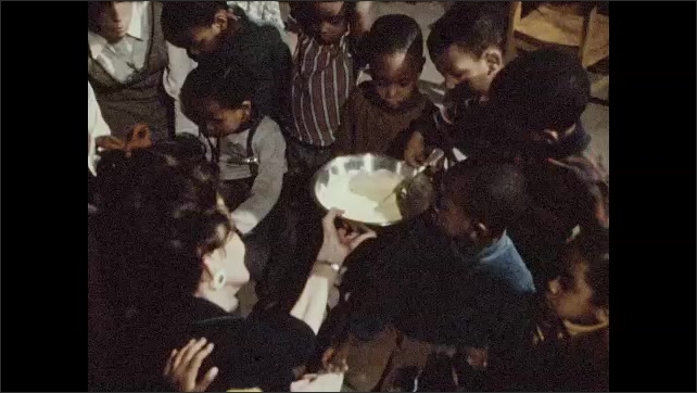 1970s: Teacher at center of circle of seated children holds a silver bowl. The teacher gives students a turn stirring the ingredients in the bowl.