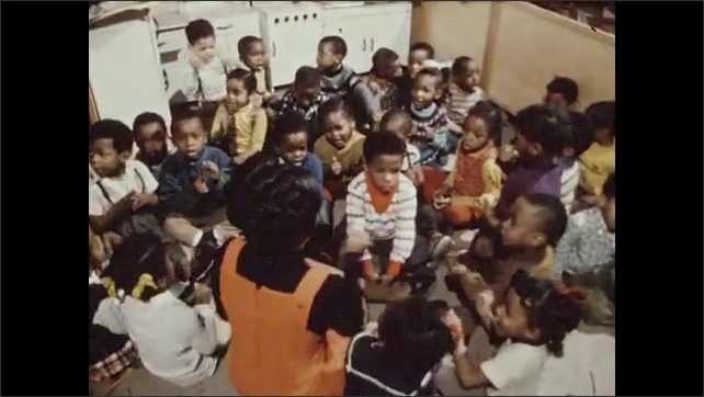 1970s: Teacher sits on her knees facing a group of mostly African American students. Teacher leads the kids in an action song and most of the students sing and move along.