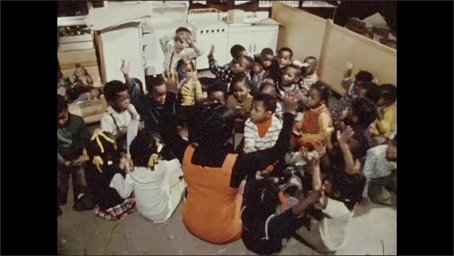 1970s: Teacher sits cross legged facing a group of mostly African American students. Teacher leads the kids in an action song and most of the students sing and move along.