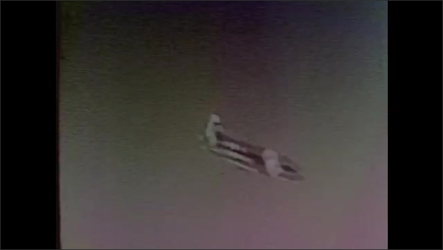 1960s: Airplane wings move.  Plane flies.  Plane drops smaller aircraft.