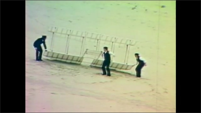 1960s: Men carry aircraft on sand dunes.  Men run to raise aircraft into air.  Man on flying machine.