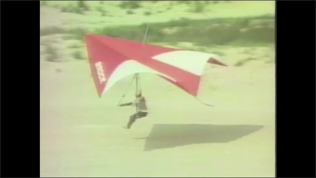 1960s: Hang glider takes off and flies.  Man lands.  People watch.  Sand dunes.