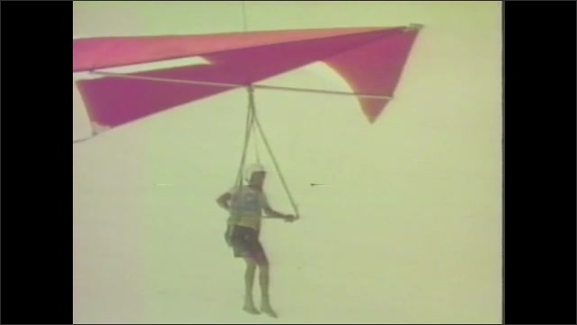 1960s: Hang glider runs off top of dune and glides through air.  Sand.  Glider lands.
