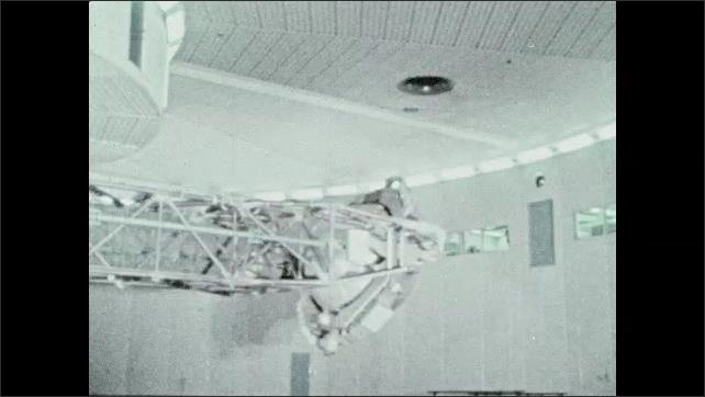 1960s: Flight accelerator spins around. Man's face on video screen. Men in zero gravity simulator.