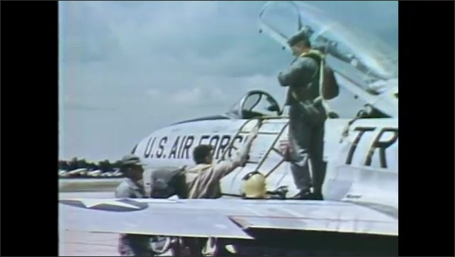 1960s: Air Force pilots put on gear and climb into cockpit of fighter jet.
