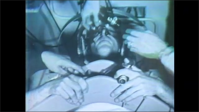 1960s: Box that is rotating comes to a halt. Man leans through window and box and talks to man in box. Tube removed from man's mouth. Blindfolded man in moving chair operates hand control.